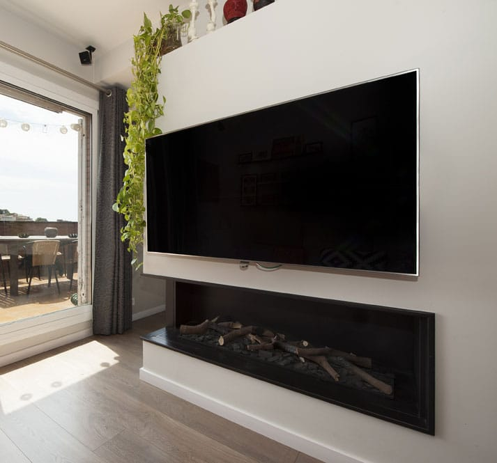 Chimenea de gas integrada en la pared debajo del televisor