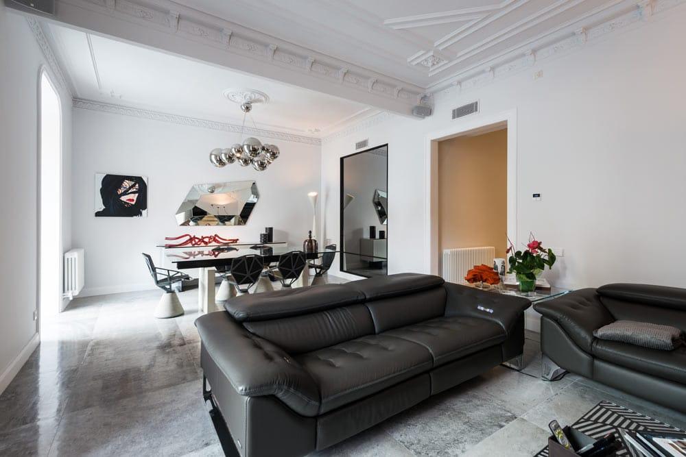 Zona de estar con zona de Tv y comedor. Color negro y blanco.