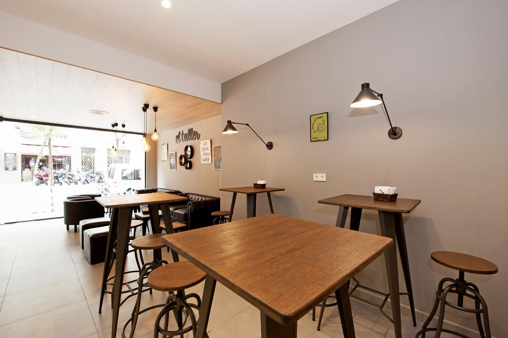 Mesas altas y taburetes de color marrón iluminados con apliques en la pared.