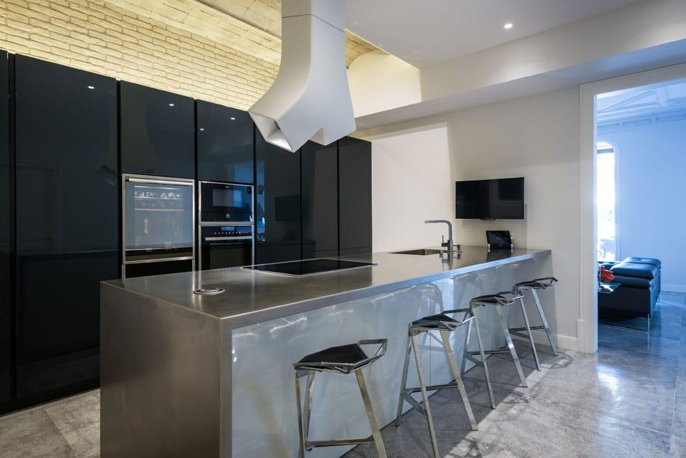 Cocina de diseño hecha a medida con península y barra. Color gris y negro. Piso en Eixample de Barcelona