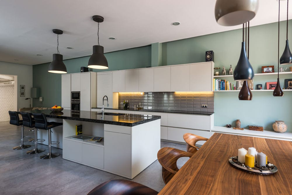 Cocina con isla y con barra con taburetes. Loft en Barcelona