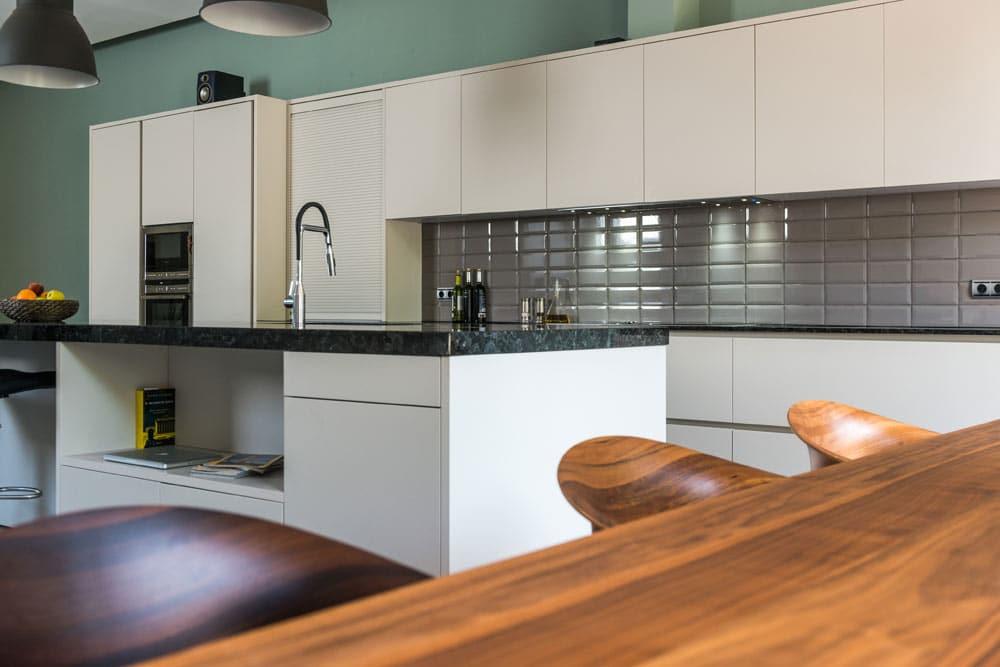 Cocina con isla y mobiliario columna en blanco. Loft industrial en Barcelona.