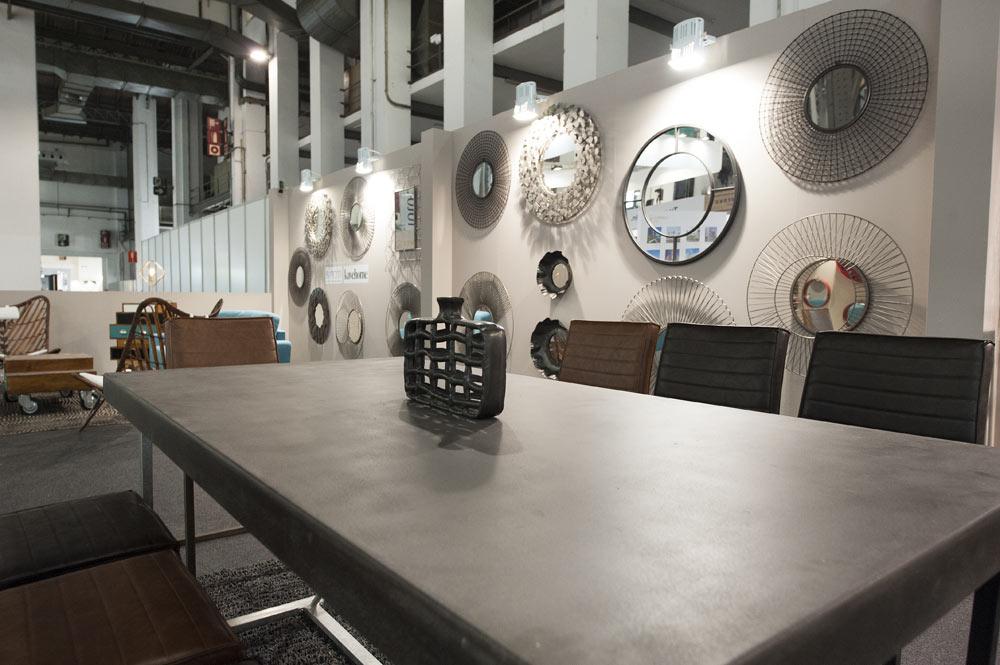 Mesa grande en gris oscuro con sillas de piel en negro y marrón. Y composición de espejos en la pared