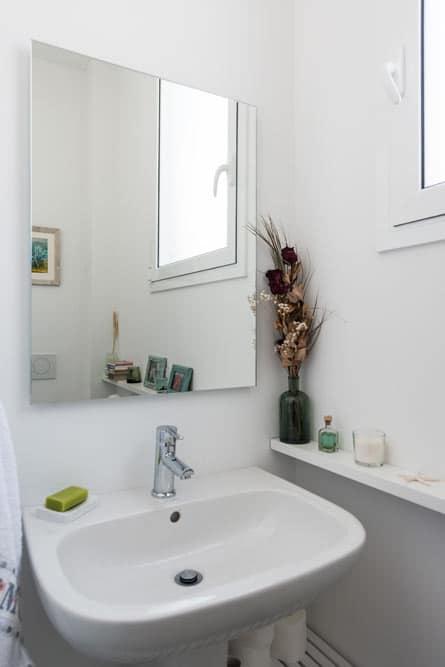 Pequeño lavabo de un aseo de color blanco