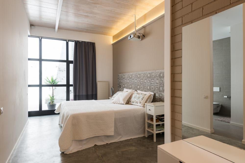Dormitorio tipo suite con tonos claros.