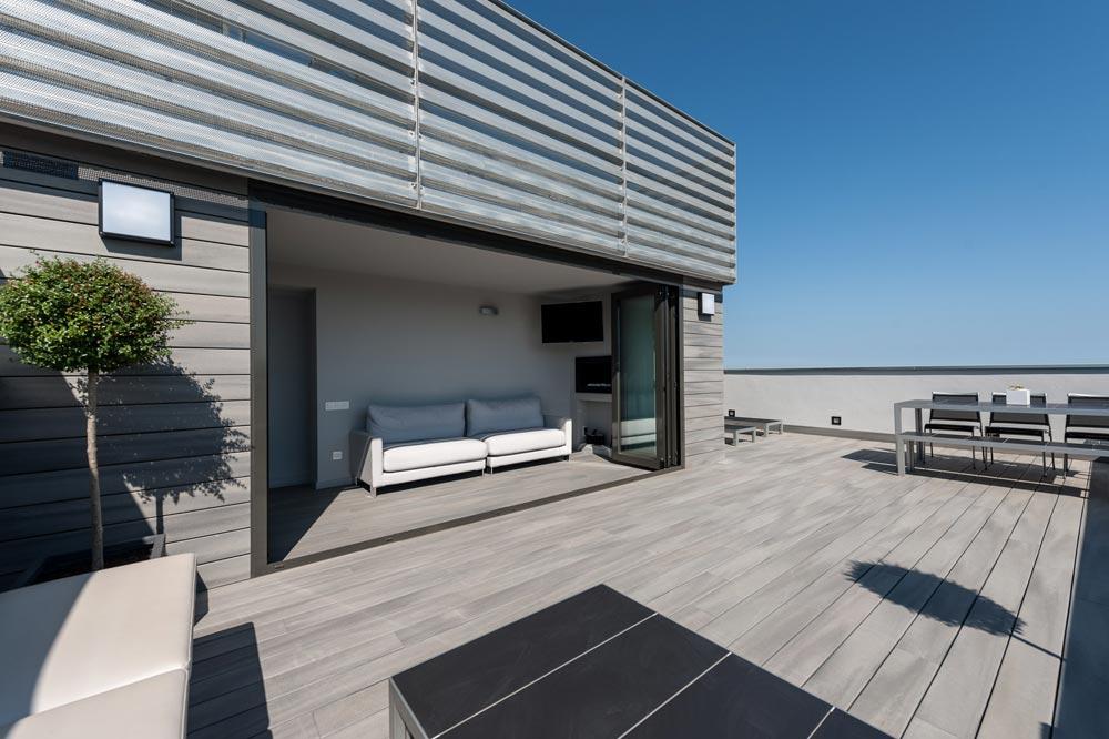 Terraza con porche con sistema de cierre en Barcelona. Con pavimiento de madera en gris.