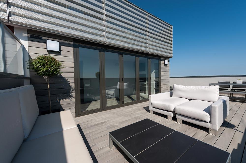 Zona de relax / chill out terraza en un ático de Barcelona. Tonos grises.