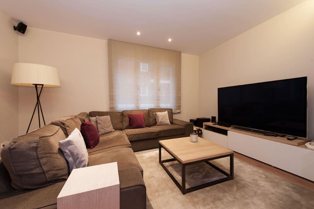 Espacio de sofá esquinero con mesita y televisión TV. Reforma de pisos en Barcelona.