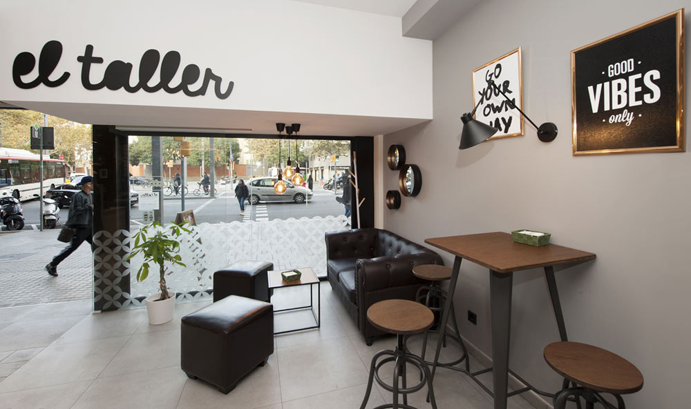 Zona de relax cafetería con sofás y mesas altas. Color marrón y negro