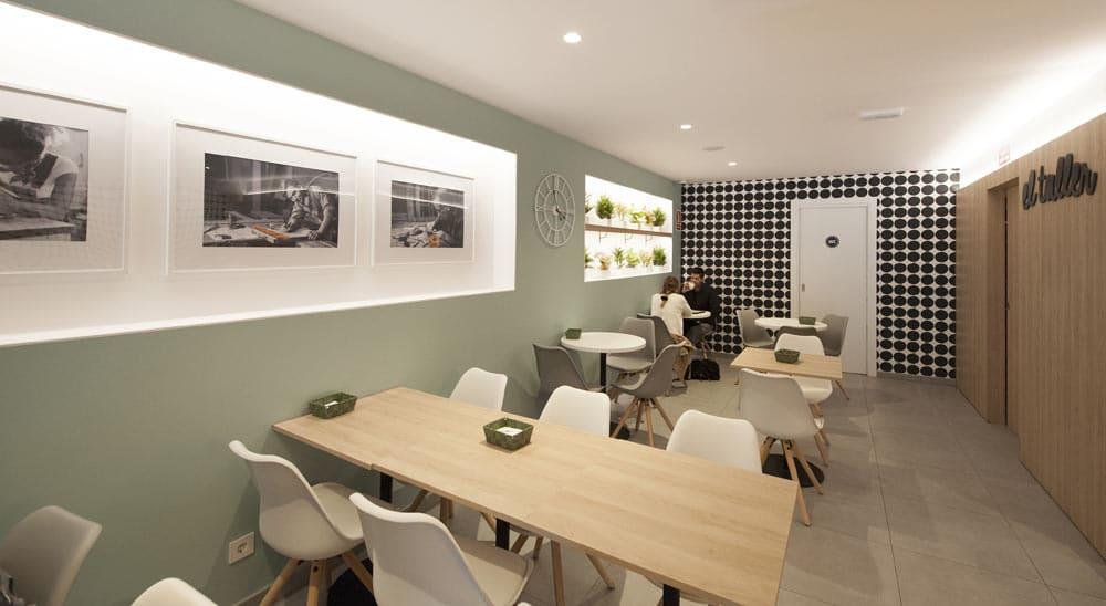 Decoración de cafetería con nichos, cuadros, plantas y papel pintado