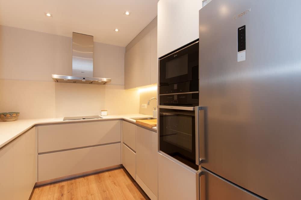 Cocina en forma de U con armarios columna para almacenamiento y electrodomésticos.