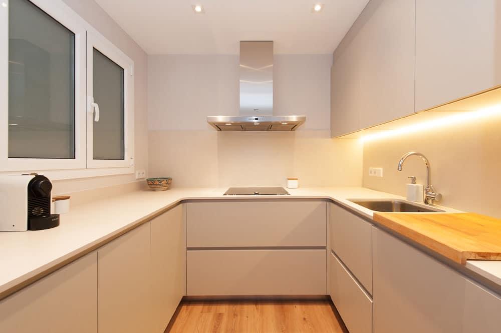 Cocina moderna en forma de U. Blanco y gris claro.