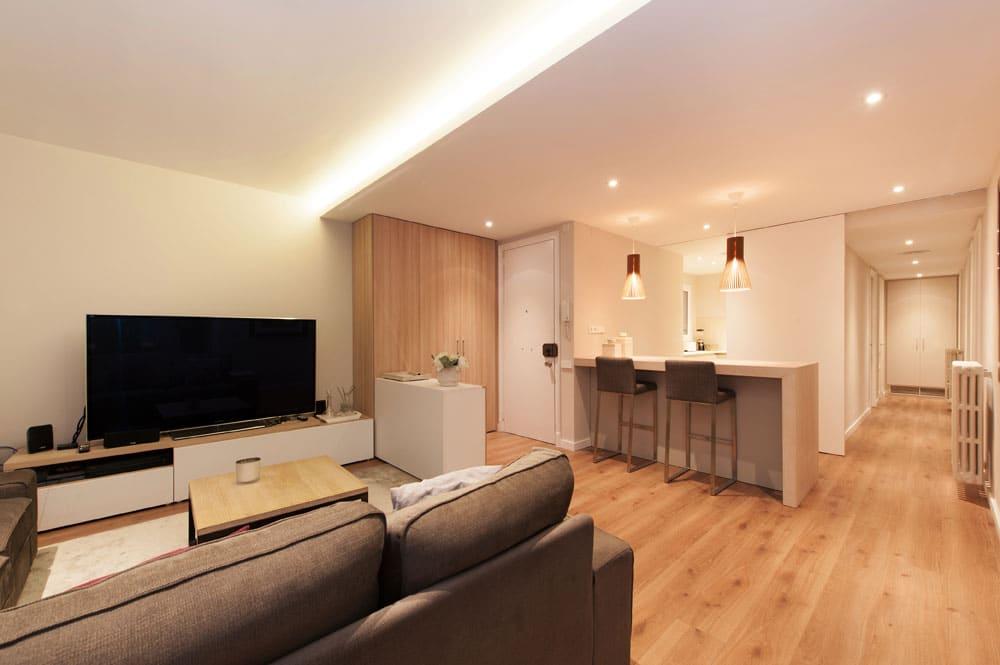 Salón con zona de TV y cocina semi abierta. Proyecto interiorismo Sant Gervasi.