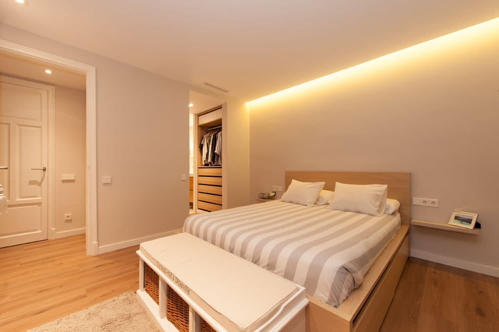 Dormitorio con cama y banquillo de pie cama. Piso ubicado en Barcelona.