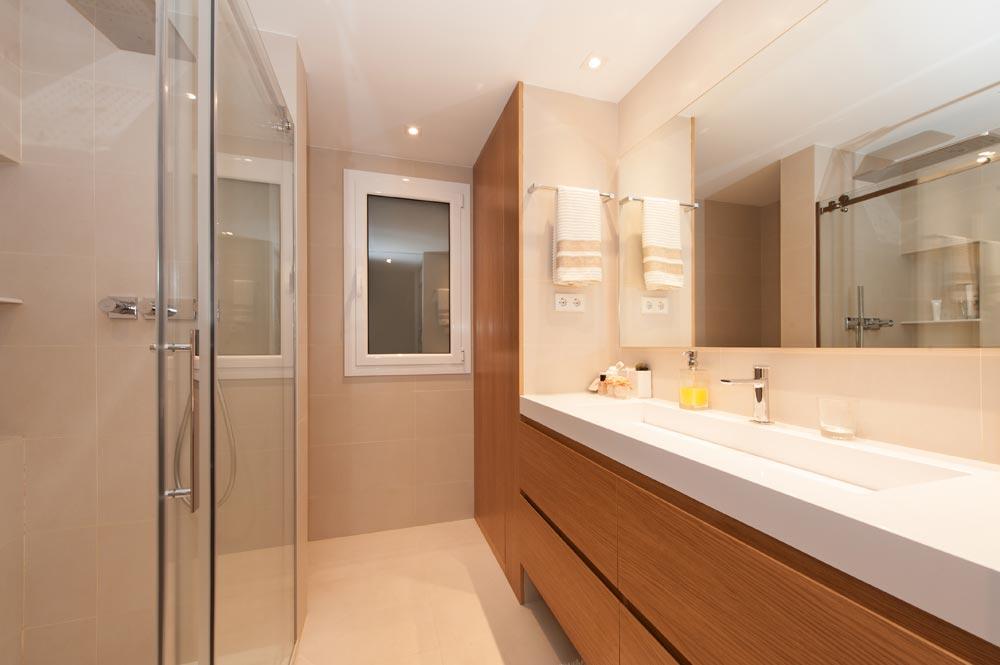 Baño en dormitorio con ducha y lavabo. Colores neutros