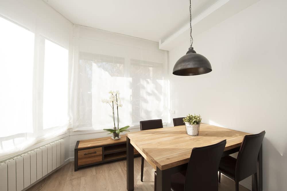 Mesa, sillas y lámpara colgante en comedor estilo nórdico industrial.