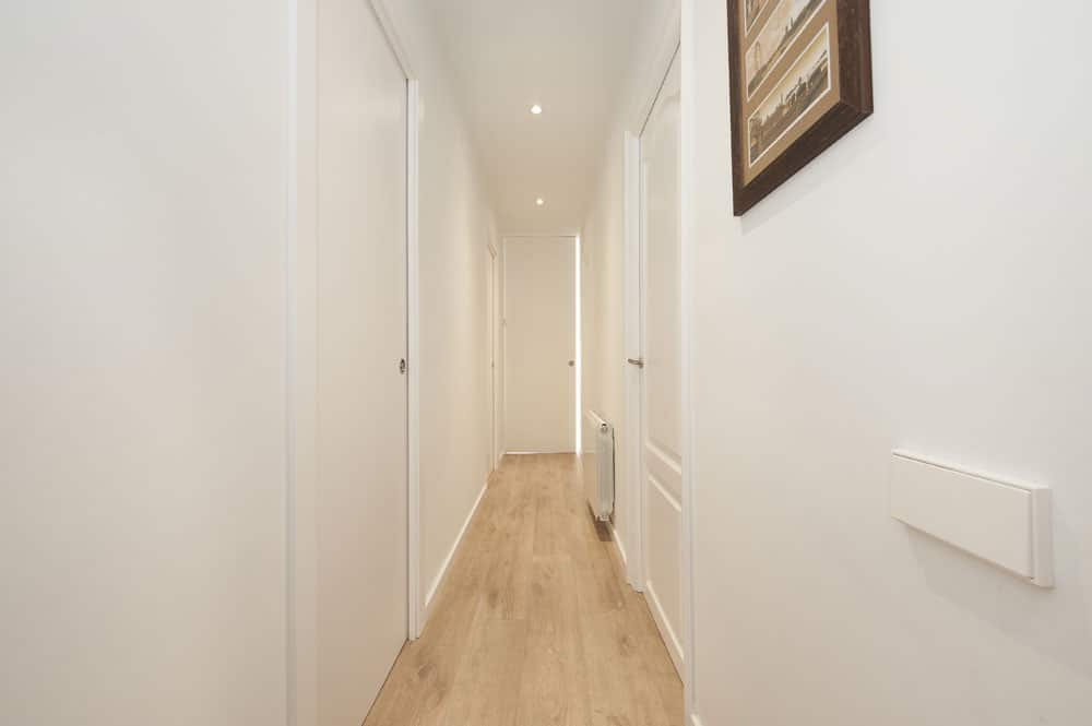 Pasillo con puerta corredera en blanco lacado que da acceso a la zona de día.