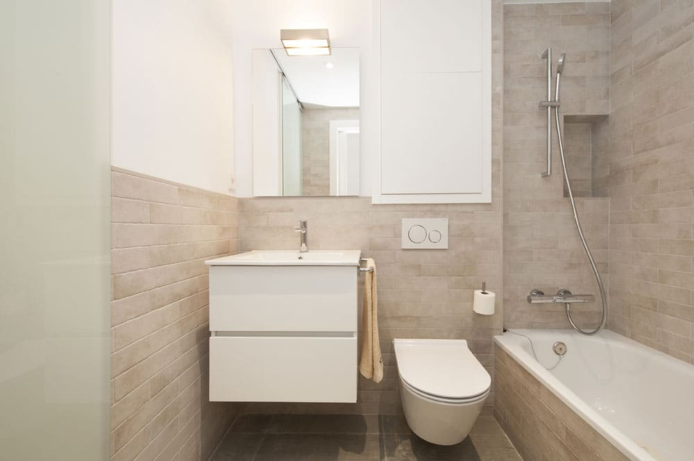 Baño con sanitarios y lavabo suspendido. Bañera integrada.