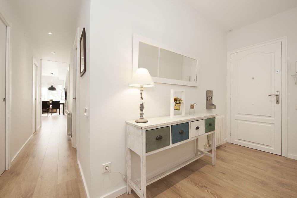 Recibidor y pasillo del piso. Suelo parquet y paredes en color blanco. Reforma realizada por Sincro.