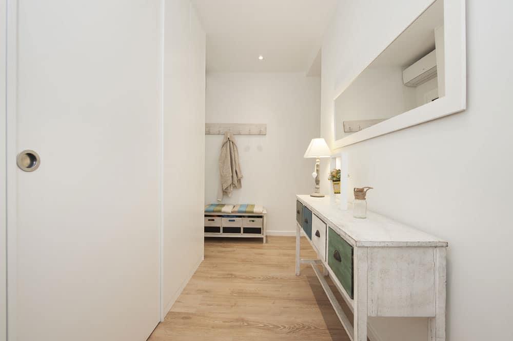 Recibidor. Muebles de color blanco con efecto envejecido. Suelo parquet madera color claro.
