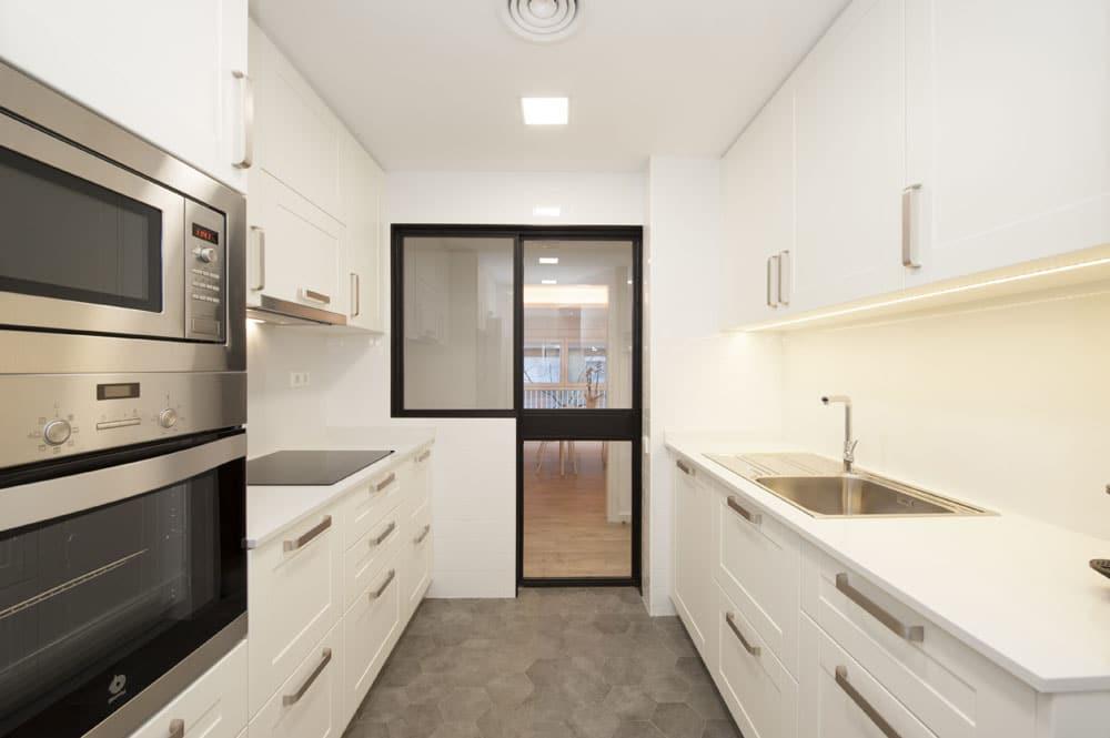 Mobiliari de cuina a mida de color blanc. Reforma de cuina realitzada per Sincro.