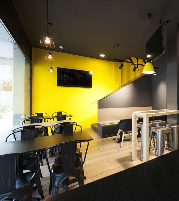 Zona de mesas restaurante en color negro y amarillo. Planta baja. Diseño Sincro