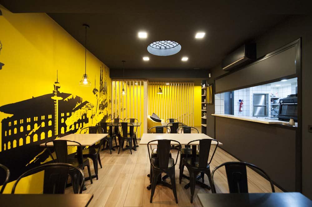 zona de mesas restaurante color negro y amarillo.