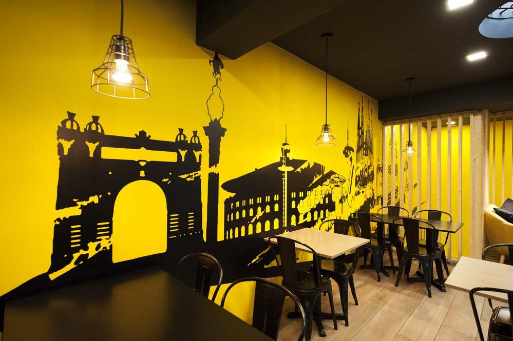 Pared con vinilo skyline barcelona en color amarillo y negro en una de las paredes de la zona de mesas. Restaurante Kyoku