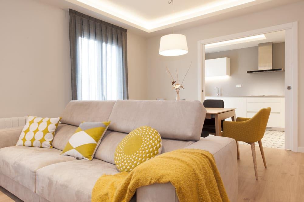 Decoración salón color mostaza. Cojines, manta y sillas. Proyecto de decoración Sincro.