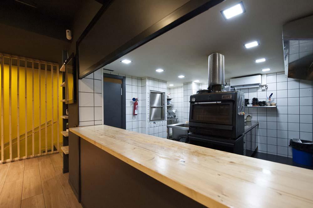 Cocina de restaurante semi abierta a la zona de mesas.