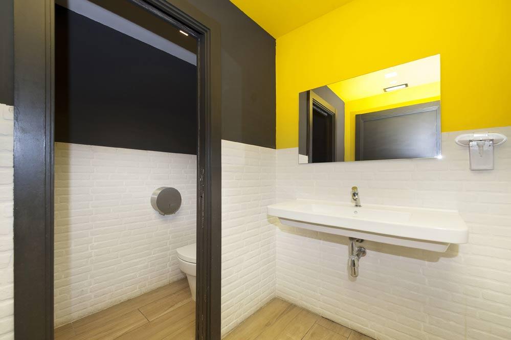 Lavabo con paredes en negro, amarillo y blanco. Diseño de restaurante Sincro