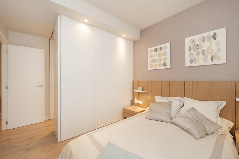 Dormitorio con vestidor privado con puerta corredera lacada en blanco