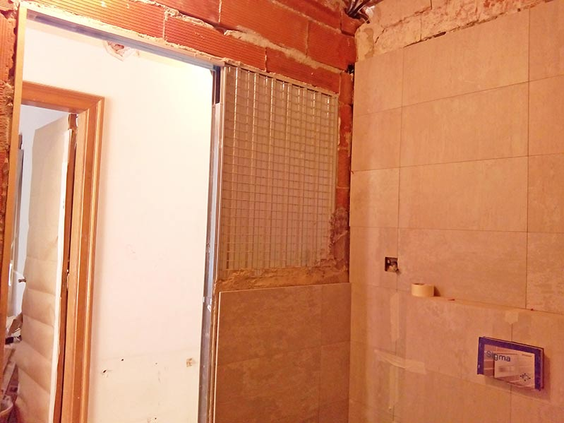 Carcasa de puerta corredera integrada en una pared de ladrillo del baños. Reforma de piso en Barcelona.