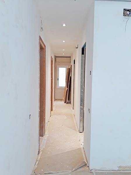 Enyesado y pintado de paredes con puertas correderas ocultas. Reforma de piso en Barcelona.