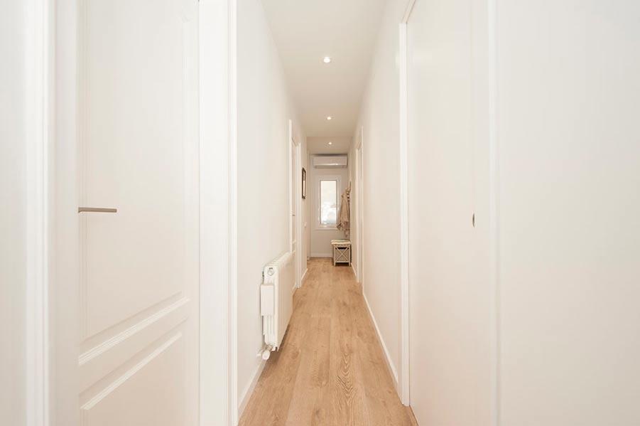 Puertas correderas empotradas a la pared del pasillo. Diseño de piso Sincro.