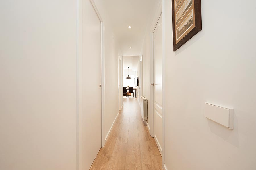 Pasillo con puertas correderas ocultas en la pared lacadas en blanco