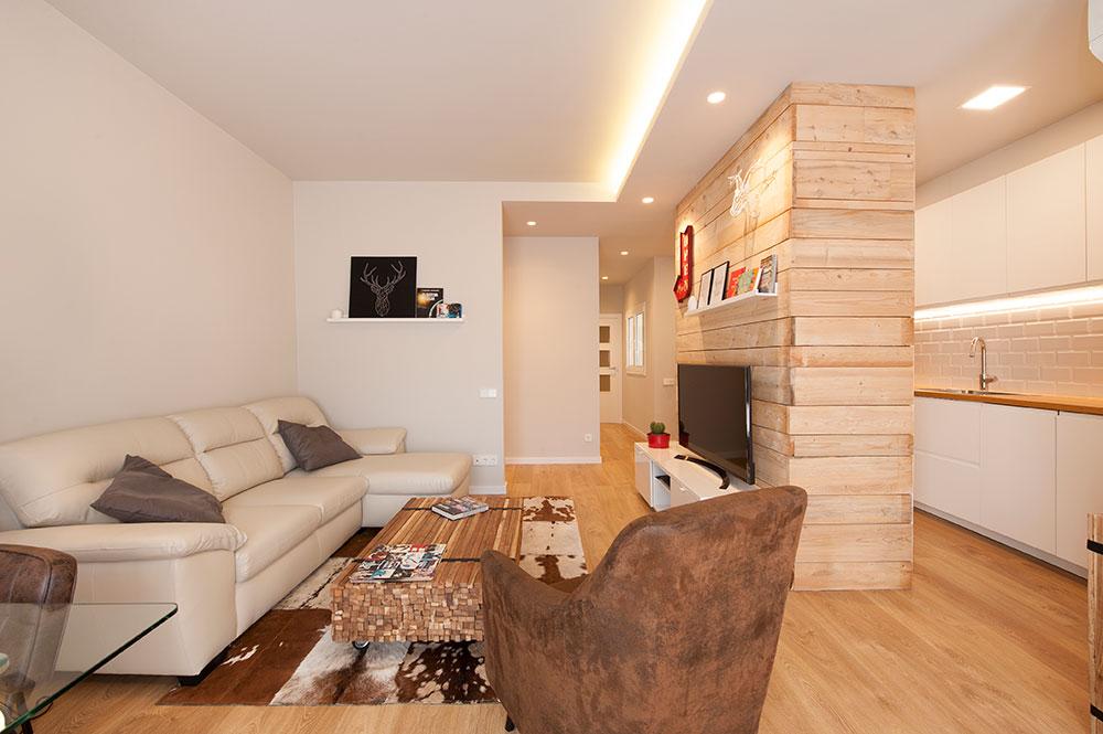 Sala de estar diáfana con la cocina. Estructura que alberga la zona de tv y columnas de mobiliario de cocina.