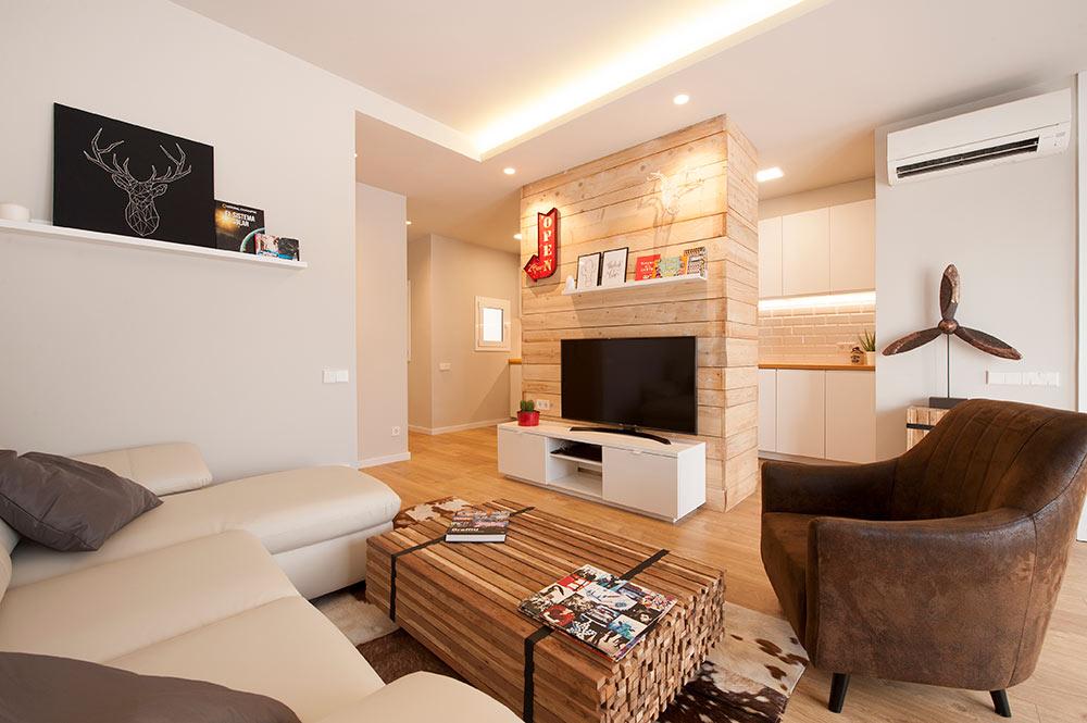 Sala de estar con la cocina semi abierta detrás de la zona de TV. Sincro