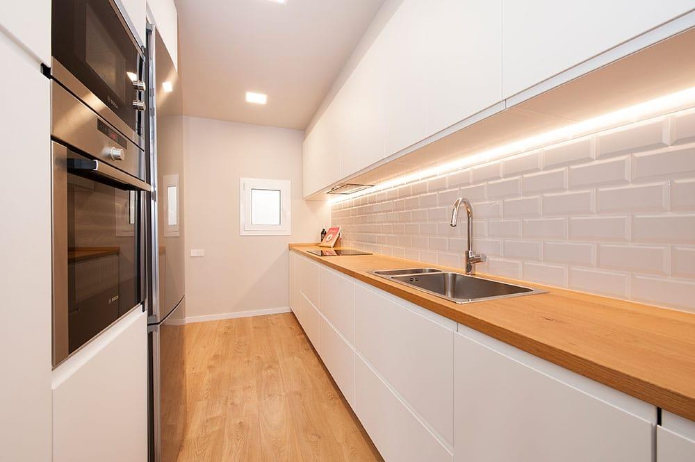 Cocina moderna de color blanca con encimera de madera. Salpicadero baldosa metro.