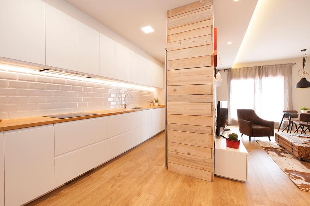 Mueble cocina revestido con madera para separar cocina y salón dentro de un espacio abierto.