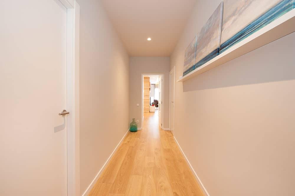 Pasillo distribuidor de habitaciones en paredes color gris claro.