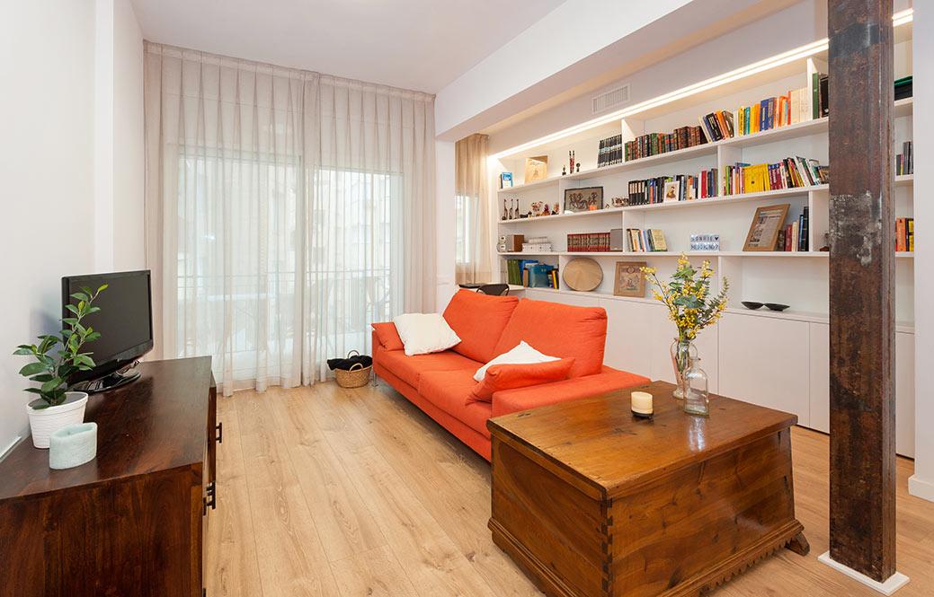Sala d'estar amb moble de llibreria i sofà de color taronja.