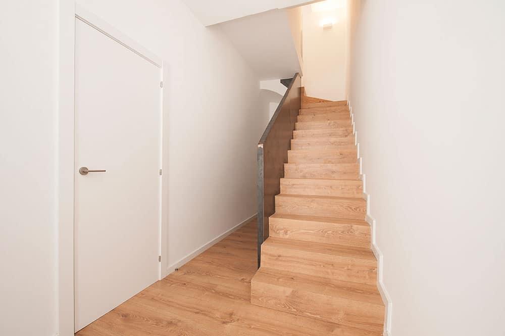 Entrada casa adosada. Escalera con revestimiento de madera y barandilla de hierro - Sincro