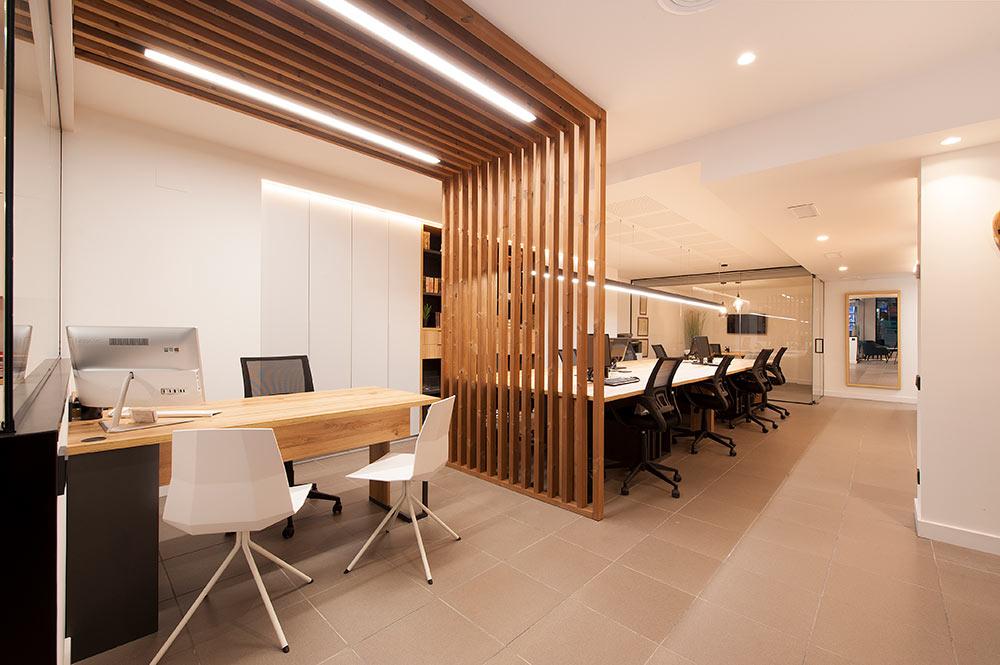 Estructura de listones de madera con tiras Led que hace de divisoria interior oficina.