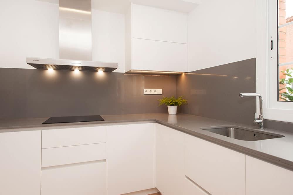 Cocina blanca con encimera y salpicadero en color gris.