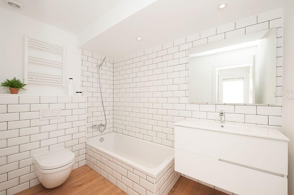 Cuarto de baño con baldosa tipo metro blanca y juntas negras.