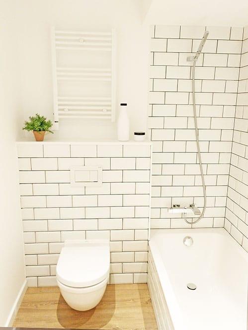 Baño con baldosas tipo metro blanco y juntas negras. Sanitario suspendido. Reformas de baño Sincro.