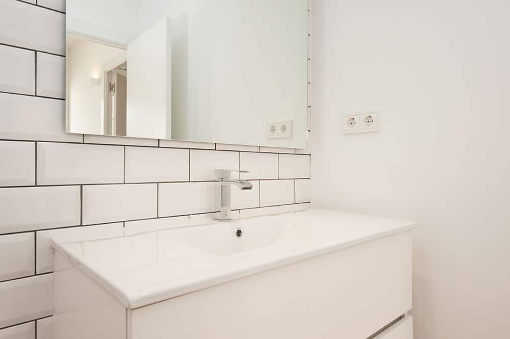 Lavabo con paredes azulejos tipo metro en blanco y juntas negras.