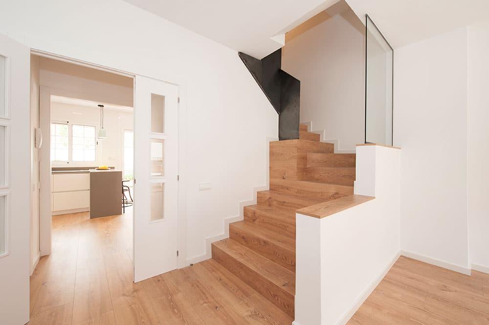 Escalera con revestimiento de madera y barandilla maciza de hierro.