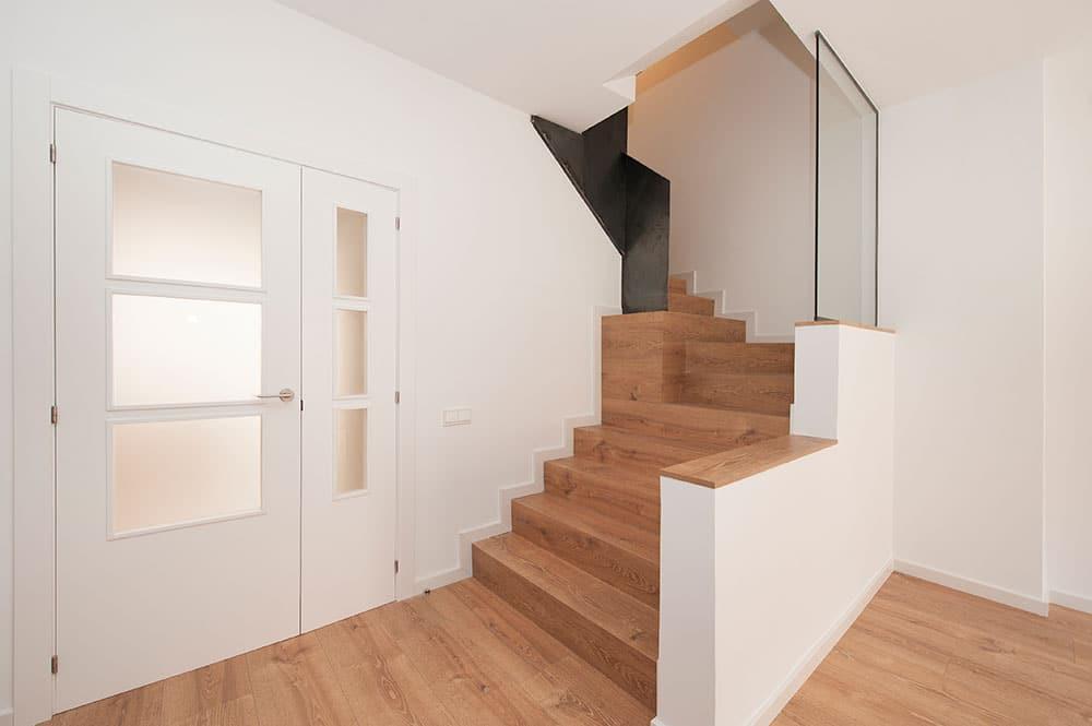 Puerta de madera acristalada en vidrio translúcido y escalera.